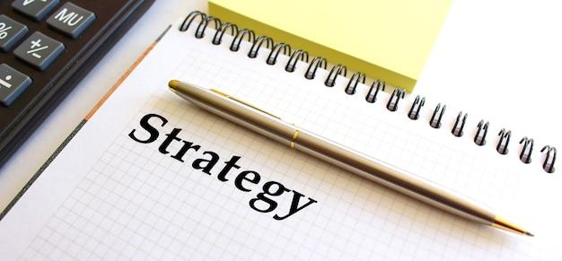 Blocco note con testo strategia, accanto si trova una calcolatrice e fogli di nota gialli.