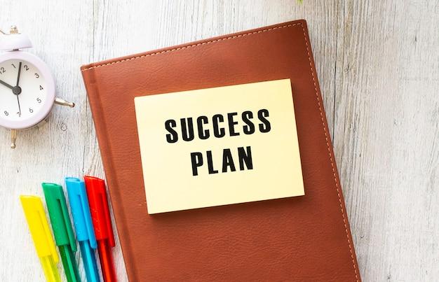 Blocco note con testo piano di successo su sfondo bianco, vicino a laptop, calcolatrice e forniture per ufficio. concetto di affari.