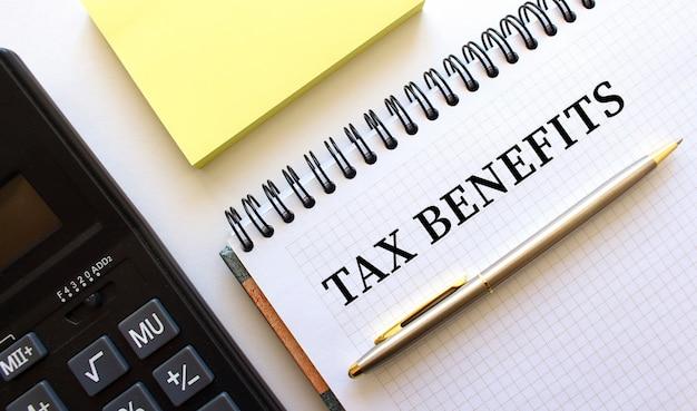 Blocco note con testo vantaggi fiscali, accanto ad esso si trova una calcolatrice. concetto di affari.