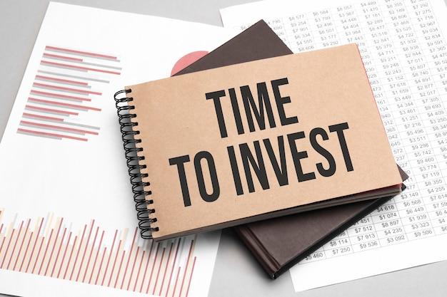 Blocco note con testo tempo per investire su uno sfondo bianco, vicino a laptop, calcolatrice e forniture per ufficio. concetto di affari.