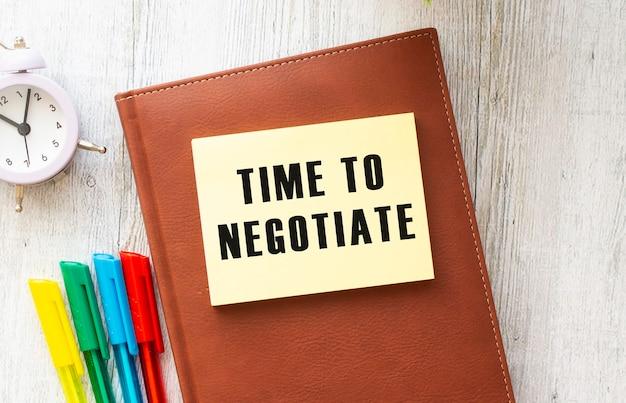 Blocco note con testo tempo di negoziare su uno sfondo bianco, vicino a laptop, calcolatrice e forniture per ufficio. concetto di affari.