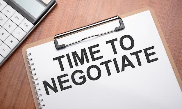 Blocco note con testo è ora di negoziare su sfondo di legno con clip, penna e calcolatrice