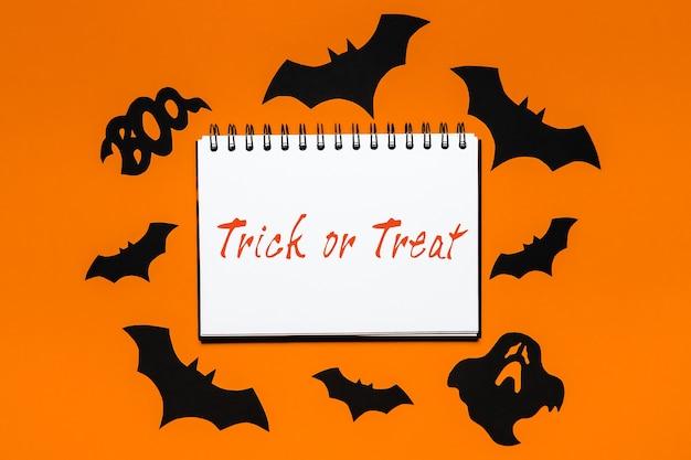 Blocco note con testo dolcetto o scherzetto su sfondo bianco e arancione con pipistrelli, zucche e fantasmi