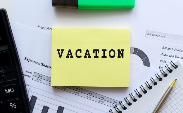Blocco note con testo vacanza su uno sfondo bianco, vicino a penna e calcolatrice. concetto di affari.