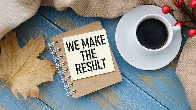 Blocco note con testo facciamo il risultato su un tavolo di legno, vicino a calcolatrice e forniture per ufficio. concetto di affari.