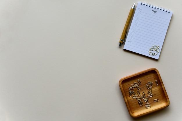 Blocco note con penna in legno e vassoio in legno con punti metallici dorati su fondo di carta beige. vista dall'alto. copia spazio. lay piatto.