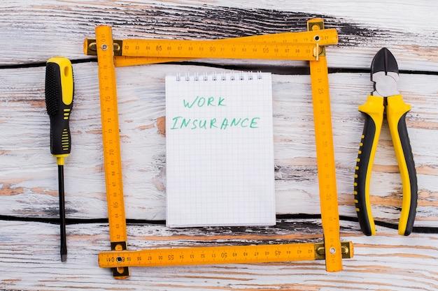 Blocco note con nota di assicurazione sul lavoro in una cornice di righello. cacciavite e pinze sul tavolo di legno bianco.