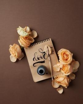 Blocco note con parola scritta amore e fiori su un tavolo marrone, piatto laici