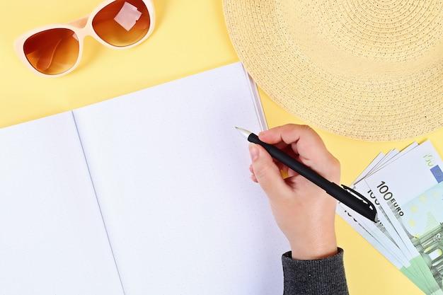 Blocco note sfondo giallo, occhiali da sole, cappello, soldi. vista dall'alto. copia spazio. sfondo estivo, viaggi.