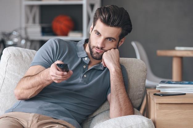 Niente di interessante da guardare. bel giovane che tiene il telecomando e sembra annoiato mentre guarda la tv sul divano di casa