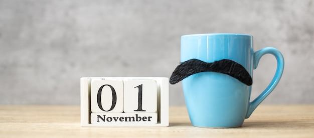 Calendario del 1 novembre, tazza da caffè blu o tazza da tè e decorazioni con baffi neri sul tavolo. giornata degli uomini, felice festa del papà e ciao concetto di novembre
