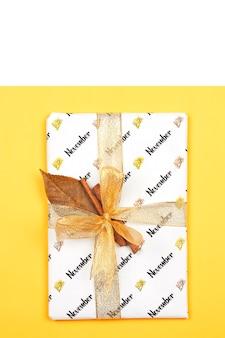 Confezione regalo di novembre su nastro dorato brillante e foglia d'autunno