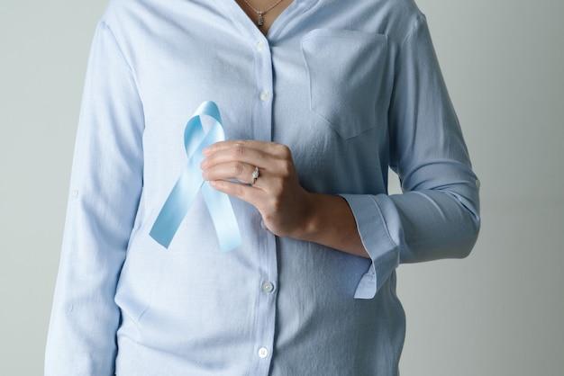 Nastro azzurro di novembre sulla mano della donna mese di consapevolezza del cancro alla prostata