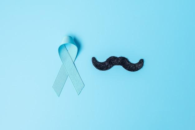Novembre mese di consapevolezza del cancro alla prostata, nastro azzurro con baffi su fondo in legno per sostenere le persone che vivono e le malattie. più lontano, la giornata internazionale degli uomini e il concetto di giornata mondiale del cancro