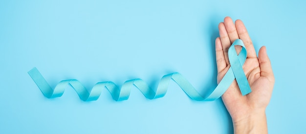 Novembre mese della consapevolezza del cancro alla prostata, uomo che tiene un nastro azzurro chiaro per sostenere le persone che vivono e le malattie. assistenza sanitaria, uomini internazionali, padre, giornata mondiale del cancro e concetto di giornata mondiale del diabete