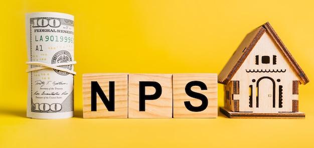 Nps con modello in miniatura di casa e denaro su sfondo giallo. investimenti, immobili, casa, alloggio, guadagni, concetto finanziario