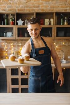 Il marito nudo in grembiule tiene il vassoio con il dessert dolce in cucina. persona di sesso maschile nudo che prepara la colazione a casa, preparazione del cibo senza vestiti
