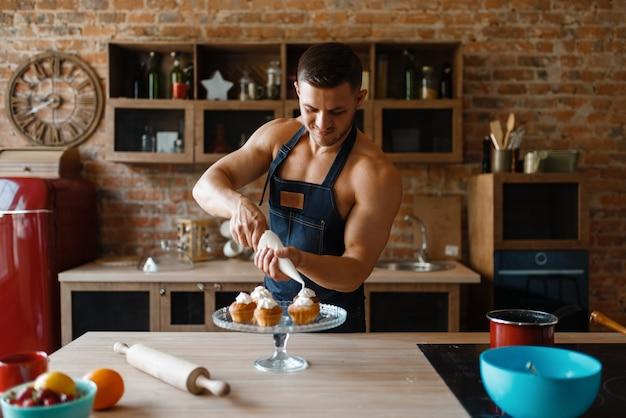 Uomo nudo in grembiule da cucina dessert in cucina. persona di sesso maschile nuda che prepara la colazione a casa, preparazione del cibo nudo