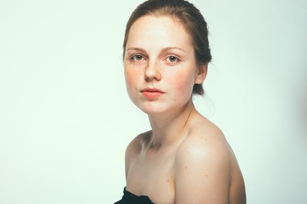Nude spalle belle lentiggini donna viso ritratto giovane. sfondo blu.