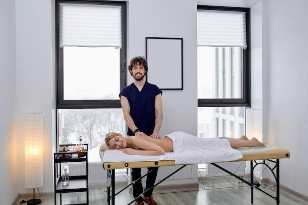 Donna nuda che gode del massaggio. vista laterale su una bionda mezza nuda con un corpo perfetto, sdraiata sulla pancia e le mani del massaggiatore che le massaggiano la schiena, spazio libero
