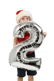 Numero 2 da un palloncino d'argento nelle mani di un ragazzo biondo con un cappello rosso di babbo natale
