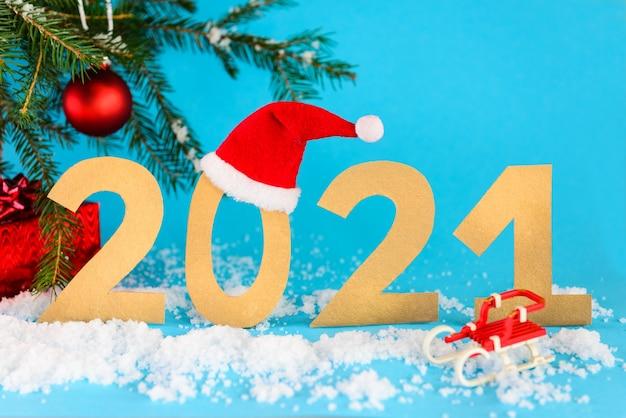 Numero 2021 nella neve sullo sfondo dell'albero di natale.