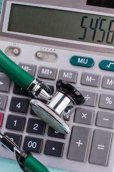 Il numero sulla calcolatrice è un simbolo del prezzo della salute. stetoscopio che pone sulla calcolatrice.