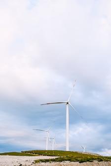 Un certo numero di turbine eoliche industriali nel campo, sullo sfondo di cieli nuvolosi
