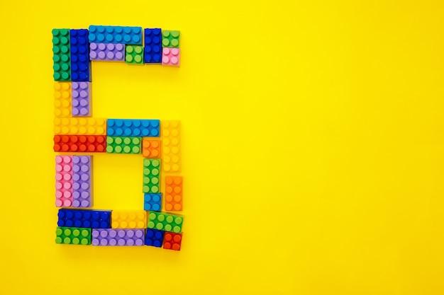 Il numero sei del costruttore multicolore dei bambini su uno sfondo giallo. spazio vuoto per il testo.data di vacanza.