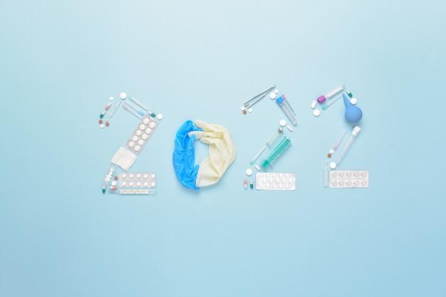I numeri 2022 sono disposti con articoli medici su uno sfondo azzurro. cartolina di natale a tema per le vacanze. capodanno e natale. farmaco. minimalismo.