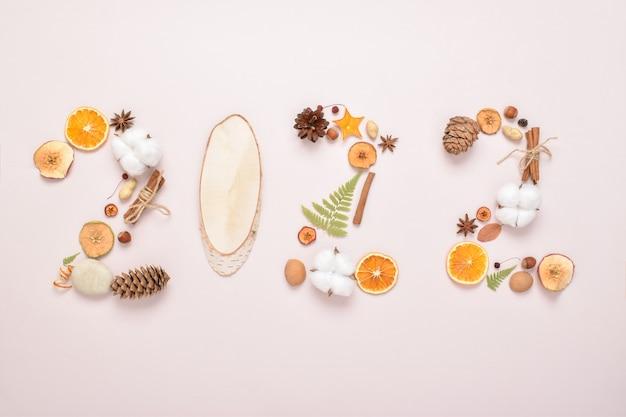 I numeri 2022 sono disposti con ingredienti naturali su fondo beige. cartolina di natale a tema per le vacanze. capodanno e natale. ecodesign. minimalismo.