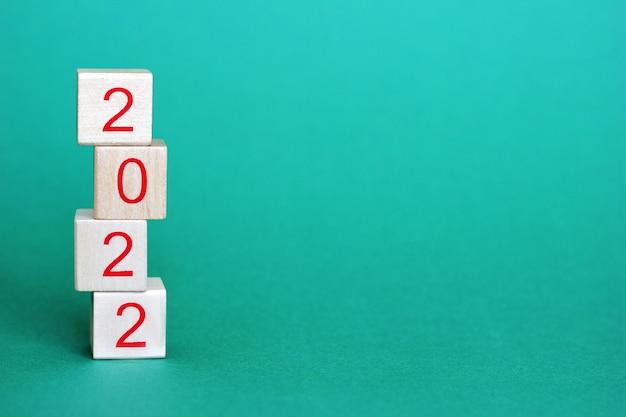 I numeri 2022 sono su blocchi di legno che stanno in una piramide uno sopra l'altro su uno sfondo verde. nuovo anno 2022 concetto. buon anno.