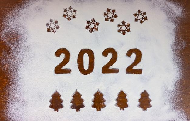 Numeri 2022, fiocchi di neve e alberi di natale disegnati sulla farina su un tavolo di legno.
