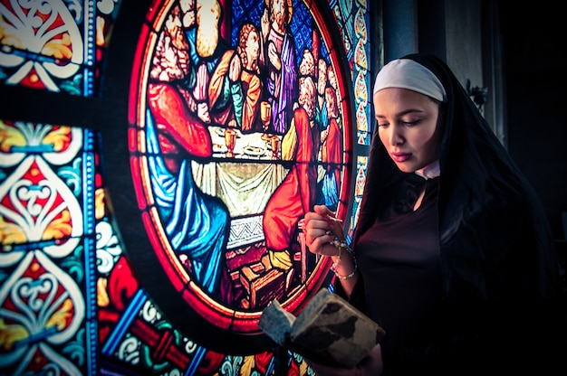 Suora che prega in un monastero