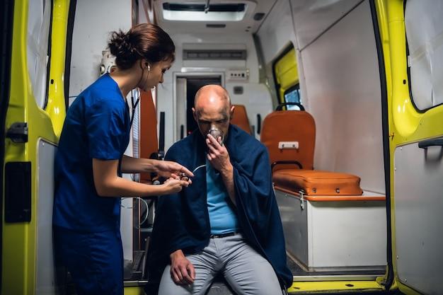 Una infermiera con uno stetoscopio sta controllando il battito cardiaco della sua paziente.