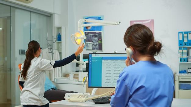 Infermiera che risponde al telefono facendo appuntamenti dal dentista in un moderno ufficio attrezzato, mentre il dentista specialista con maschera facciale sta esaminando il paziente con mal di denti seduto su una sedia stomatologica.