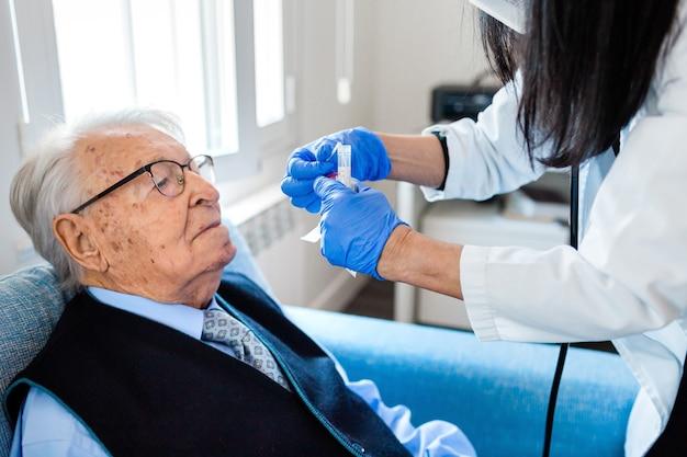 L'infermiera con guanti sanitari blu solleva la testa di un uomo anziano in camicia blu e cravatta per eseguire il test covid mentre è seduto sul divano a casa. assistenza sanitaria domiciliare.