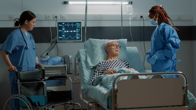 Infermiera che porta la sedia a rotelle al paziente nel letto del reparto ospedaliero