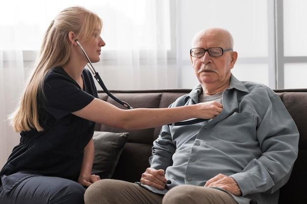 Infermiera che controlla il battito cardiaco del vecchio