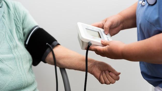 Infermiera che controlla la pressione sanguigna della donna anziana