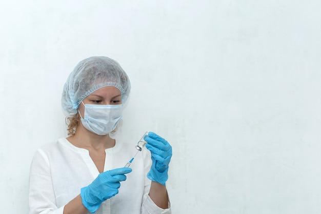 Un'infermiera compone l'iniezione nella siringa, la vaccinazione