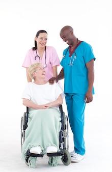 Nurse e medico con un paziente su una sedia a rotelle