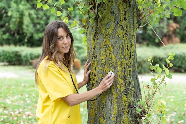 Infermiera vestita in uniforme auscultare un albero in ambiente naturale