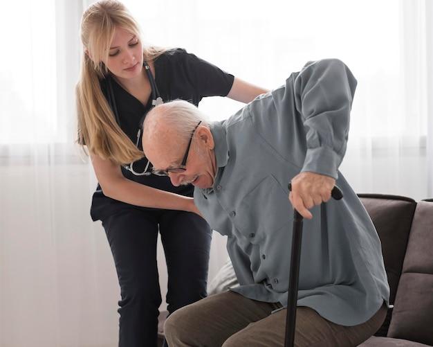Infermiera che aiuta il vecchio ad alzarsi