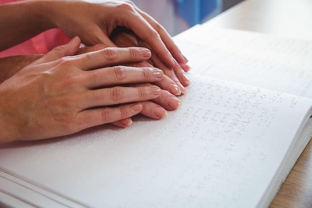 Infermiera che aiuta donna maggiore con il braille