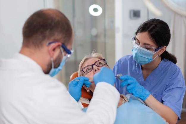Infermiera che aiuta stomatologo durante il trattamento dei denti di una paziente anziana anziana durante l'esame medico...
