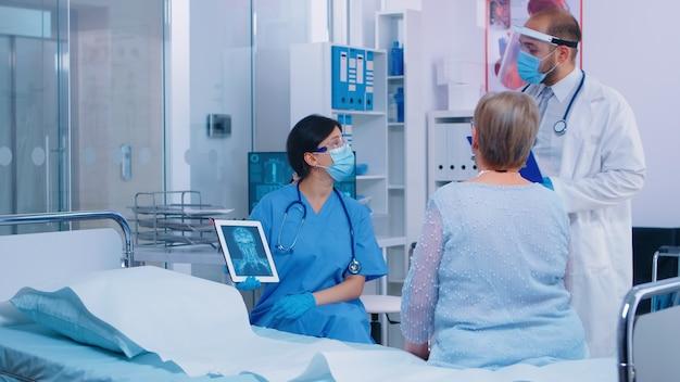 Infermiera in maschera che spiega la diagnostica su tablet pc digitale alla vecchia donna anziana in pensione mentre il medico sta entrando nella stanza d'ospedale per controllarli. sistema sanitario durante o dopo l'epidemia di coronavirus