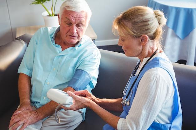 Infermiera che misura la pressione sanguigna di un uomo anziano