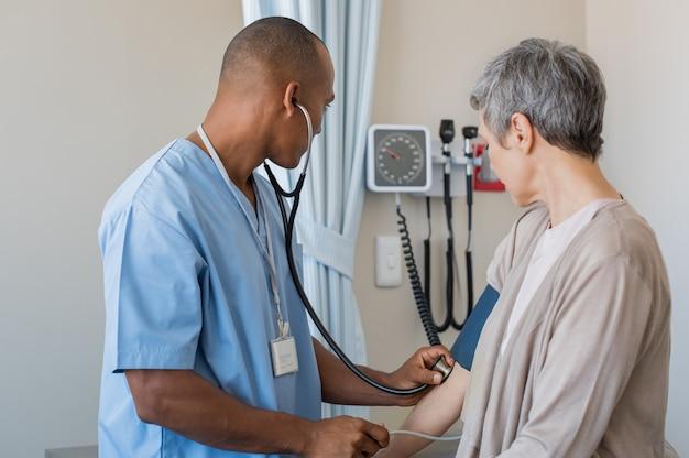 Infermiera che misura la pressione sanguigna