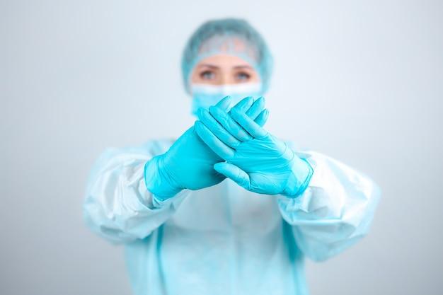 Un'infermiera in camice medico, maschera e guanti protettivi è eretta con le braccia tese in un gesto di arresto.
